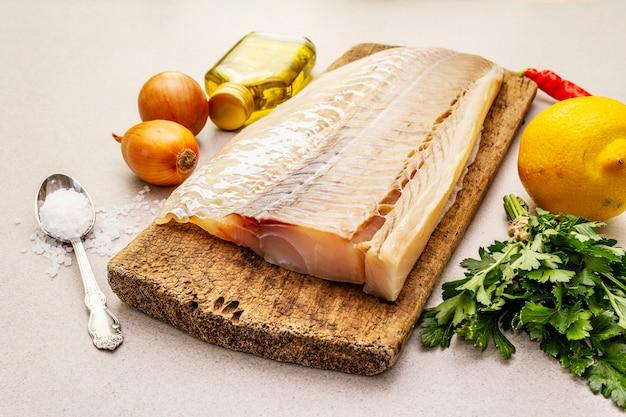 Filé de lombo de bacalhau cru com legumes, especiarias, azeite e sal.