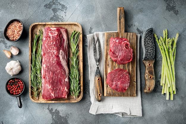Filé de lombo, ou filé de olho cortado em conjunto de carne bovina crua em mármore, em uma mesa de pedra cinza, vista de cima plano