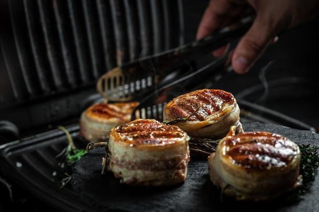 Filé de mignon grelhado lombo de carne filé de bifes de carne envolto em bacon. cozinhar bife na grelha pelas mãos do chef.