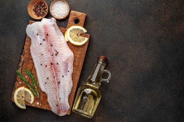 Filé de pangasius cru em uma tábua com limão, óleo e especiarias. peixe cru.