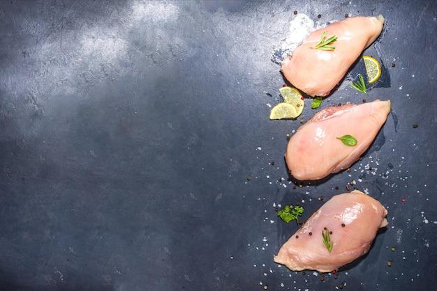 Filé de peito de frango cru em fundo escuro de concreto com especiarias e ervas para cozinhar, vista superior copie o espaço