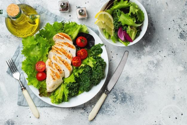 Filé de peito de frango e salada de legumes com tomate e folhas verdes. o conceito de alimentação saudável e dieta ceto. vista do topo.