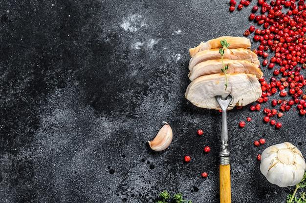 Filé de peito de frango em uma frigideira. bife grelhado. fundo preto. vista do topo. copie o espaço.