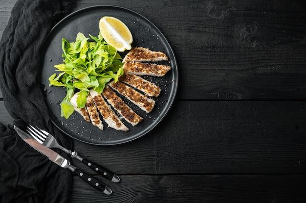 Filé de peito de frango grelhado na brasa, sobre mesa de madeira preta, vista de cima