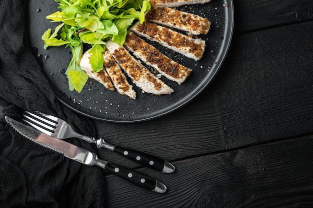 Filé de peito de frango grelhado, sobre mesa de madeira preta, plano com espaço de cópia