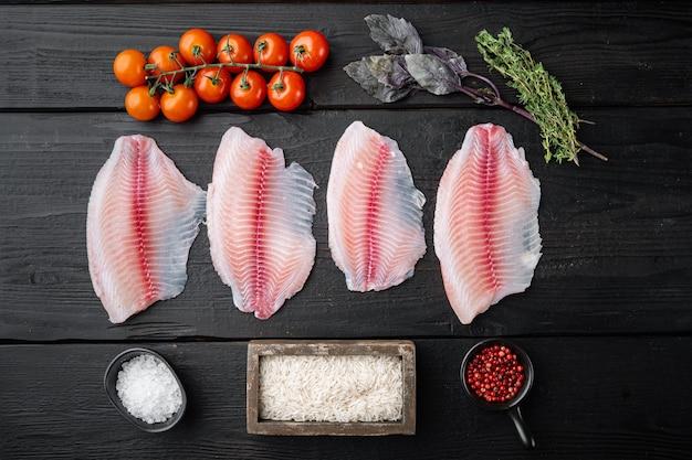 Filé de peixe branco, com ingredientes de arroz basmati e tomate cereja, em mesa de madeira preta, vista superior