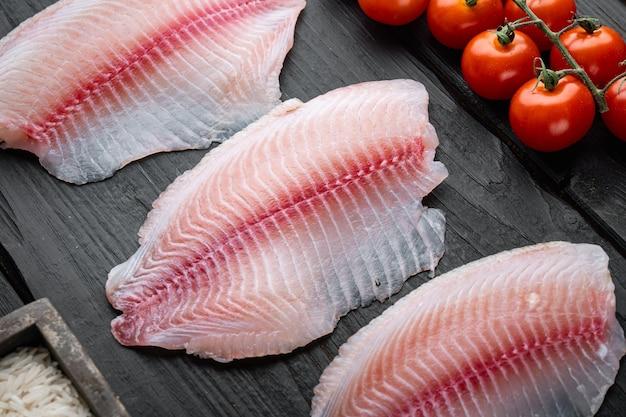 Filé de peixe branco, com ingredientes de arroz basmati e tomate cereja, em mesa de madeira preta