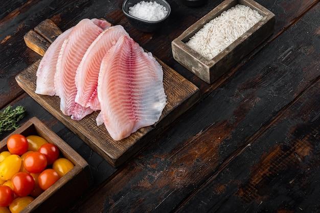 Filé de peixe branco, com ingredientes de arroz basmati e tomate cereja, em mesa de madeira velha