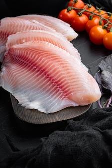 Filé de peixe branco, com ingredientes de arroz basmati e tomate cereja, na mesa preta