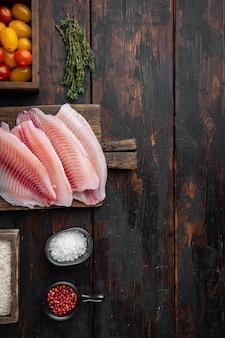 Filé de peixe branco, com ingredientes de arroz basmati e tomate cereja, na velha mesa de madeira, vista superior com espaço de cópia para o texto