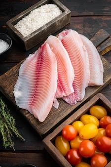 Filé de peixe branco, com ingredientes de arroz basmati e tomate cereja, na velha mesa de madeira, vista superior