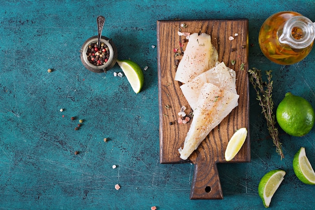 Filé de peixe branco em uma placa de madeira preparada para cozinhar. postura plana. vista do topo
