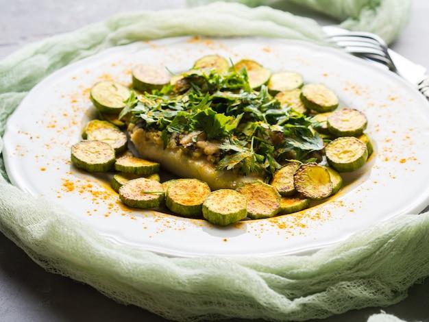 Filé de peixe cozido com cobertura de salsa de amêndoa e courgettes de açafrão na chapa branca. prato de dieta saudável