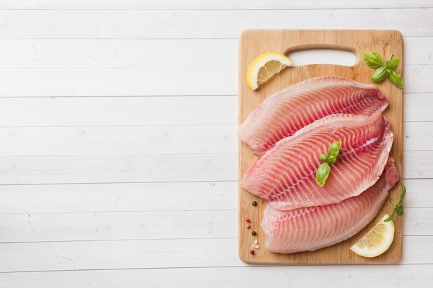 Filé de peixe cru de tilápia em uma placa de corte com limão e especiarias