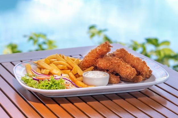 Filé de peixe e batata frita no prato branco com molho na mesa de madeira no bar da piscina do hotel fechar
