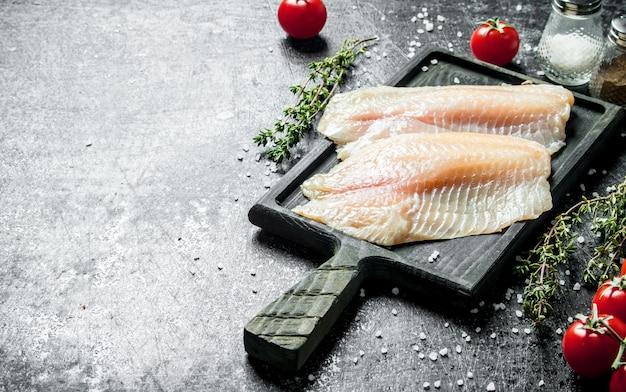 Filé de peixe em uma placa de corte com tomate e tomilho na mesa rústica preta.