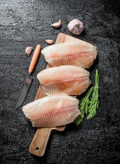 Filé de peixe em uma placa de corte com uma faca, endro e alho na mesa rústica preta.