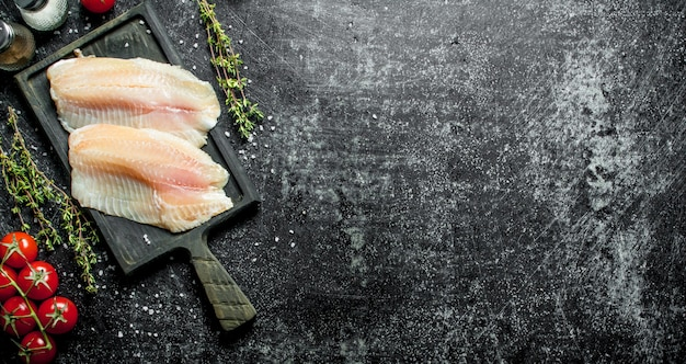 Filé de peixe em uma tábua com tomilho, especiarias e tomate em um galho na mesa rústica preta.