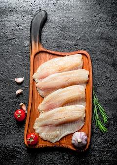 Filé de peixe em uma tábua de corte com alecrim, alho e tomate. na superfície rústica preta