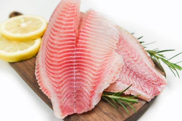 Filé de peixe fresco cortado para bife ou salada com ervas especiarias alecrim e limão - filé de tilápia cru na tábua de madeira e fundo branco e ingredientes para cozinhar alimentos