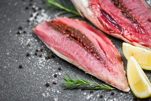 Filé de peixe fresco fatiado para bife ou salada com ervas especiarias alecrim e limão - frutos do mar peixe cru em fundo de chapa preta, atum longtail, ingredientes orientais de filé de atum pequeno para cozinhar alimentos