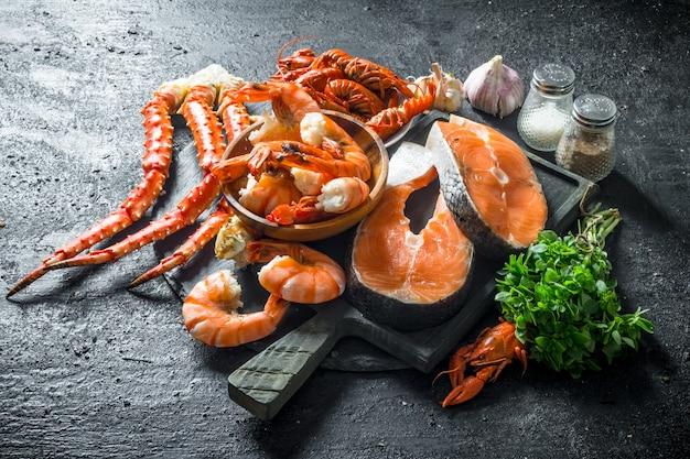Filé de peixe fresco na tábua de cortar com camarão cozido, lagostim e caranguejo.