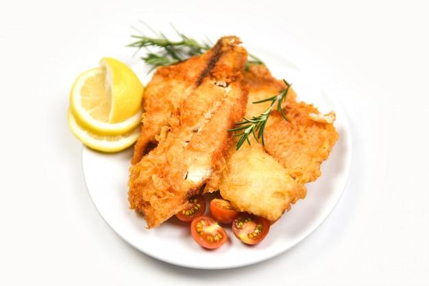Filé de peixe frito fatiado para bife ou salada cozinhar alimentos com ervas especiarias alecrim e limão / filé de tilápia crocante servido no prato