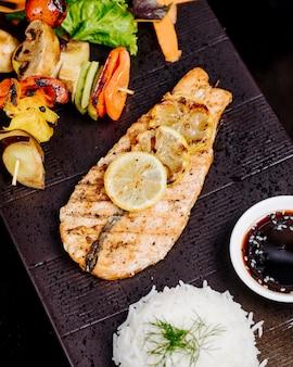 Filé de peixe grelhado com limão, churrasqueira de legumes, arroz e molho.