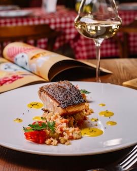 Filé de peixe grelhado servido em cima da salada de cuscuz com pimentão vertical