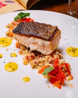 Filé de peixe grelhado servido em cima da salada de cuscuz com pimentão