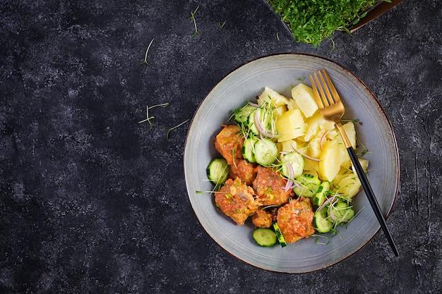 Filé de peixe no vapor com molho de tomate, batata cozida e salada de pepino fresco. refeição dietética. comida da quaresma. vista superior, acima