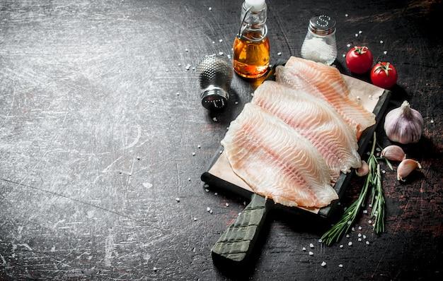Filé de peixe numa tábua de cortar com especiarias, alecrim, alho e azeite. em rústico escuro