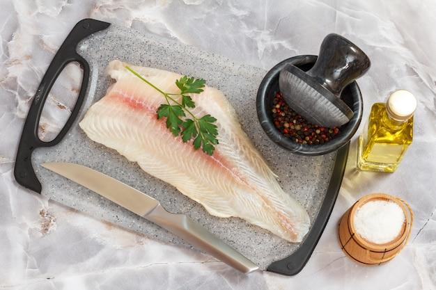 Filé de peixe pangasius cru com folhas de salsa e especiarias na tábua de cortar