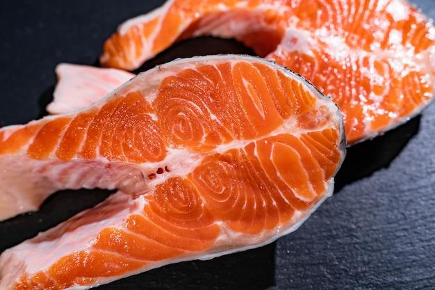 Filé de peixe salmão cru em fundo preto