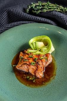 Filé de peixe salmão japonês com molho de teriyaki e abacate. fundo preto. vista do topo