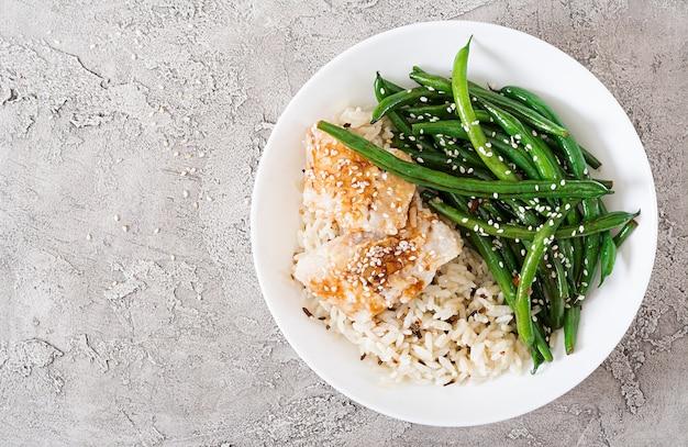 Filé de peixe servido com arroz, molho de soja e feijão verde em chapa branca. comida asiática. vista do topo. configuração plana