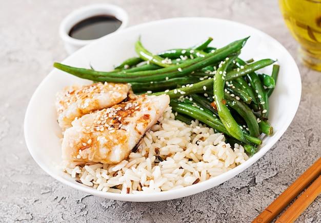 Filé de peixe servido com arroz, molho de soja e feijão verde em chapa branca. comida asiática.