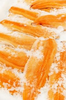 Filé de peixe vermelho com gelo no balcão da loja. fechar-se. alimentos saudáveis e vitaminas. vertical.