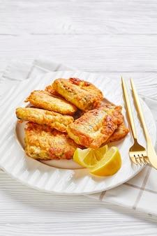 Filé de pescada crocante empanado, servido em um prato branco com fatias de limão, talheres dourados em uma superfície de madeira branca com um guardanapo, close-up