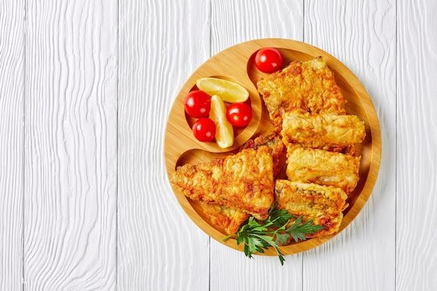 Filé de pescada crocante maltratado, servido em um prato de bambu ecológico com rodelas de limão, tomate cereja em uma superfície de madeira branca, close-up, cópia espaço, vista superior
