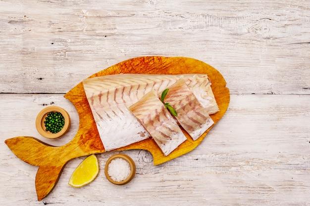 Filé de pescada cru. limão, sal, especiarias. o conceito de alimentação saudável