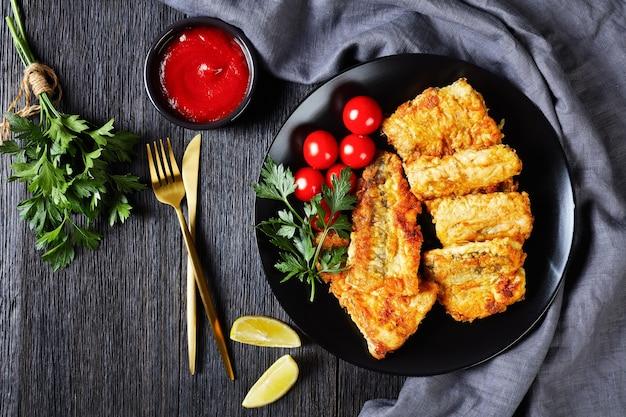 Filé de pescada frita e crocante servido em prato preto com rodelas de limão, tomate cereja, ketchup, salsa fresca em uma superfície de madeira escura