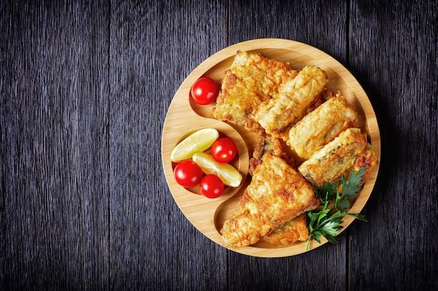 Filé de pescada frita e crocante servido em um prato de bambu ecológico com rodelas de limão, tomate cereja em uma superfície de madeira escura, close-up, cópia espaço, vista de cima