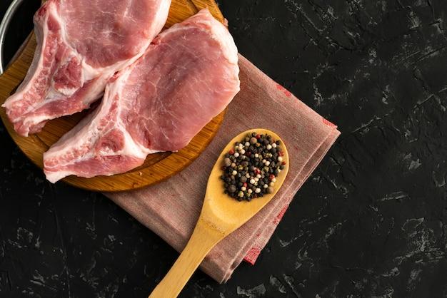 Filé de porco cru em uma tábua de cortar, colher de pau com especiarias e pimenta, junk food gordura, uncookeds