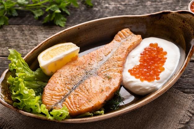 Filé de salmão assado com creme e caviar vermelho. dieta alimentar