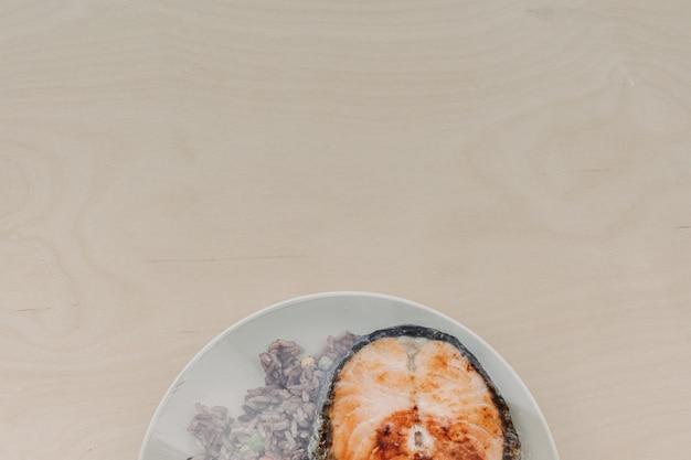 Filé de salmão com arroz frito no prato e selado com plástico