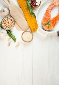 Filé de salmão com especiarias e legumes em uma mesa de luz. mesa culinária. mesa de comida. menu de mesa de mesa. copie o espaço.