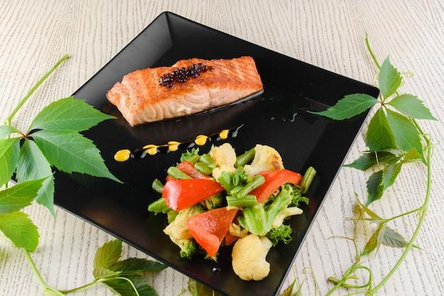Filé de salmão com legumes fritos em placas quadradas pretas sobre uma mesa de madeira branca.