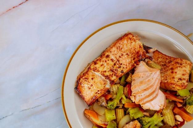 Filé de salmão com legumes salteados asiáticos. fechar-se. vista do topo.