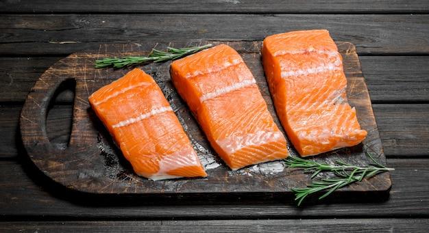 Filé de salmão cru com alecrim. em uma madeira.